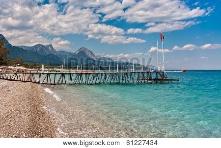 Small wooden pier on shingle beach and aquamarine water in popular touristic resort of Kemer on Mediterranean sea in Turkey.