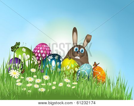 Easter bunny and eggs nestled in grass and flowers