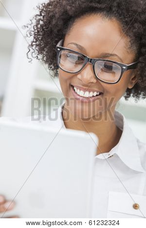 A beautiful happy mixed race African American girl or young woman wearing geek glasses & using a tablet computer in her kitchen