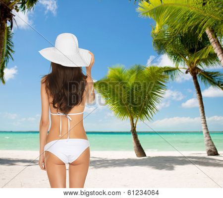 summer and holidays concept - woman posing in white bikini with hat