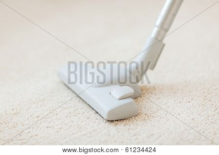 cleaning and home concept - close up of male hoovering carpet