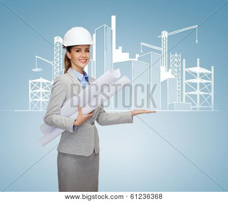 building, developing, consrtuction and architecture concept - smiling architect in helmet with blueprints showing city sketching on palm of hand