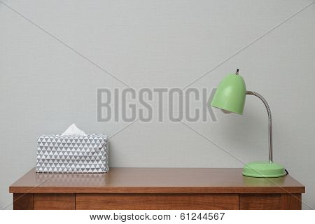 Wooden Brown Table With Lamp And Tissue In Bedroom