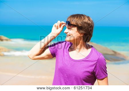 young handsome man in sunglasses smiling at beach
