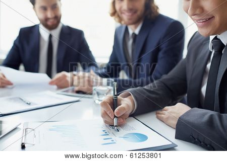 Young businessman working with spreadsheet with his colleagues on background