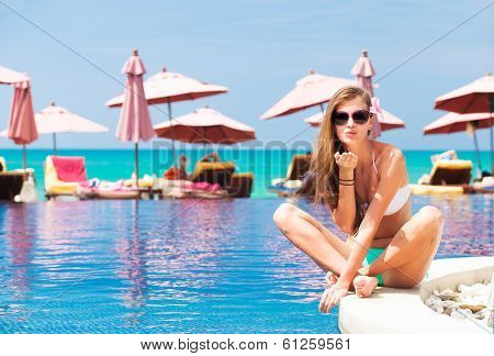 young woman near swimming pool blowing air kiss on poolside