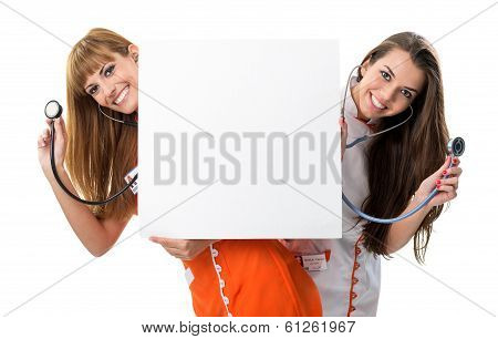 Two nurses. Look behind blank board with stethoscope