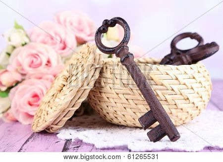 Key to success and happiness. Composition with keys in wicker basket and flowers. Conceptual photo. On color wooden table, on light background