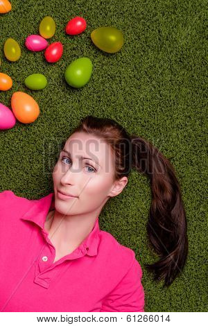 beauty female lying on green grass with easter eggs