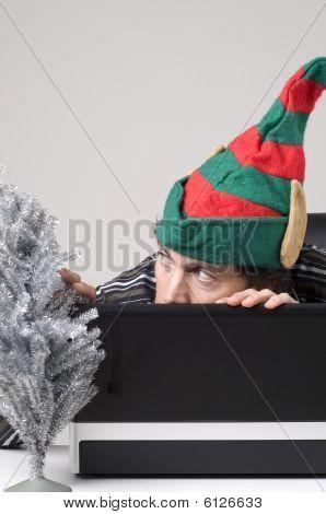 Mann versteckt sich hinter Laptop mit Elf Hut