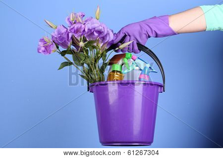 Housewife holding bucket with cleaning equipment on bright background. Conceptual photo of spring cleaning.