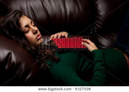 Young Lady Sleeping On Sofa After Reading A Book