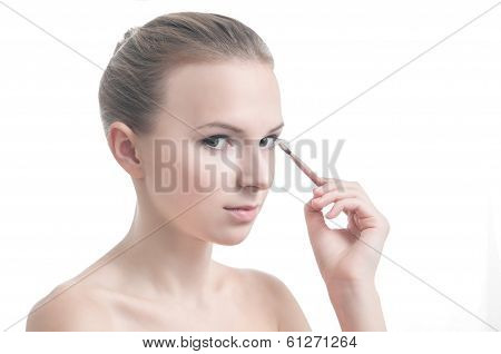 Girl with eyelid brush, isolated on white