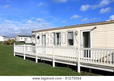Side view of modern caravan on trailer park with cloudscape background.