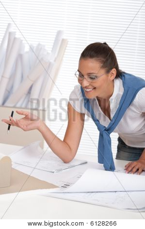Smiling Female Architect Watching Plans
