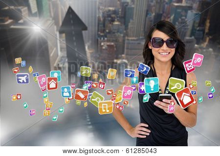 Digital composite of glamorous brunette using smartphone with app icons