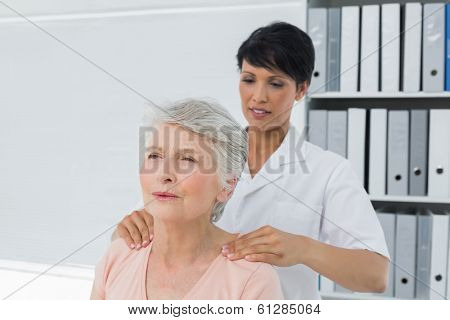 Female chiropractor massaging a senior womans shoulder in the medical office