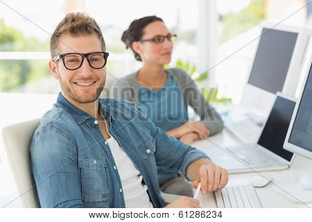 Team of smiling designers with man looking at camera in creative office