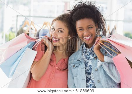 Portrait of two happy young women with shopping bags in the clothes store