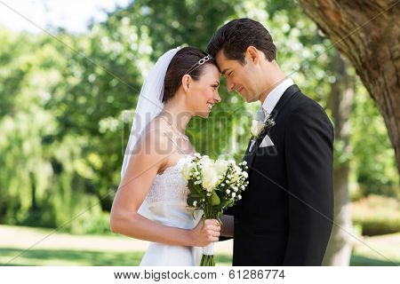 Side view of loving newly wed couple with head to head standing in garden