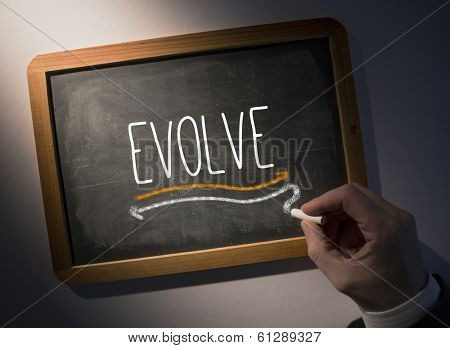 Hand writing the word evolve on black chalkboard