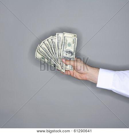 man holding bills on grey