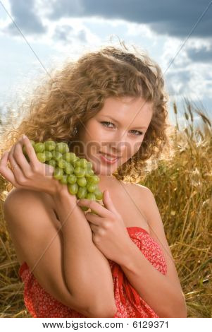 Beautiful girl on picnic in wheat field with grapes