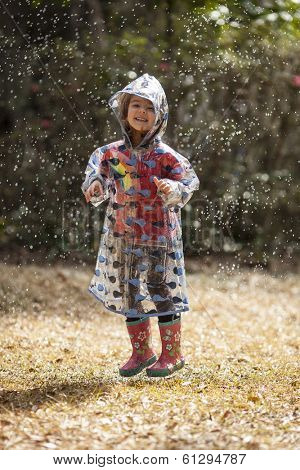 little girl in raincoat jumping in the rain