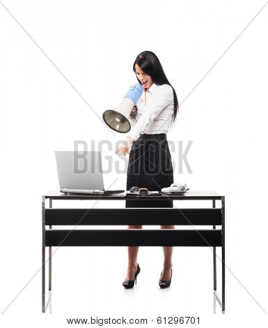 Angry and furious business woman screaming at notebook computer through a megaphone, isolated on white.