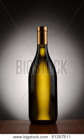 Chardonnay  wine bottle over a spot light to dark background. Bottle is without a label in vertical format.