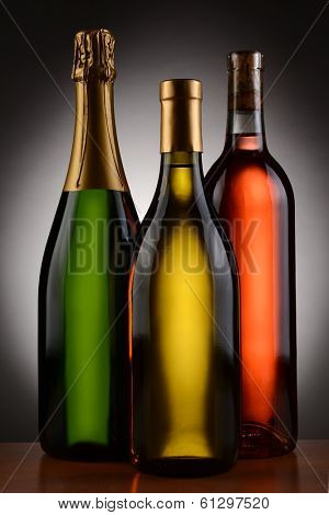 Champagne, Chardonnay and Blush wine bottles over a spot light to dark background. Bottles are without labels in vertical format.