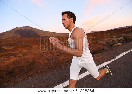 Man running on road in beautiful nature. Male runner sprinting during workout training for marathon on mountain road at night. Young Caucasian fitness model with copy space.