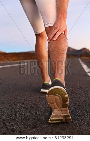 Cramps in leg calves or sprain calf on runner. Sports injury concept with running man outside.