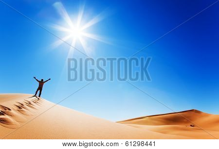 Success concept: rear view of a adult white man standing on a sand dune and holding arms up. Erg Chebbi, Morocco.