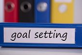picture of goal setting  - The word goal setting on blue business binder - JPG