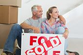 Happy couple sitting on floor with sold sign in their new home