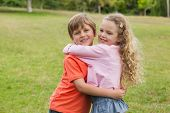 Portrait of two smiling kids hugging at the park
