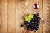 Red wine glass and grape on wooden table background with copy space