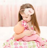 stock photo of doll  - Cute smiling little girl playing with a doll at home - JPG