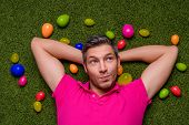 stock photo of insole  - man lying green grass springtime with easter eggs - JPG