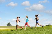 Female friends running downhill through sunny meadow summer sport