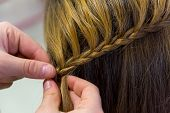 stock photo of braids  - Hairdresser makes braids in beauty salon - JPG