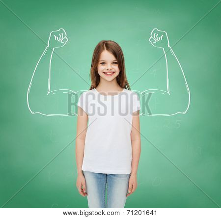advertising, school, education, childhood and people - smiling little girl in white blank t-shirt over green board background with strong arms drawing
