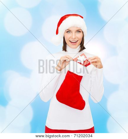 christmas, winter, happiness, holidays and people concept - smiling woman in santa helper hat with small gift box and stocking over blue lights background