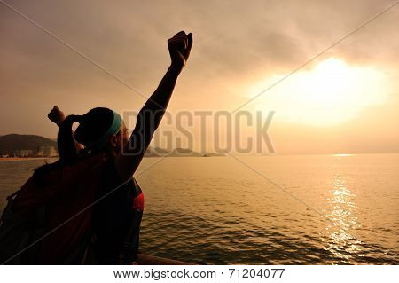cheering hiking woman open arms to the sunrise seaside