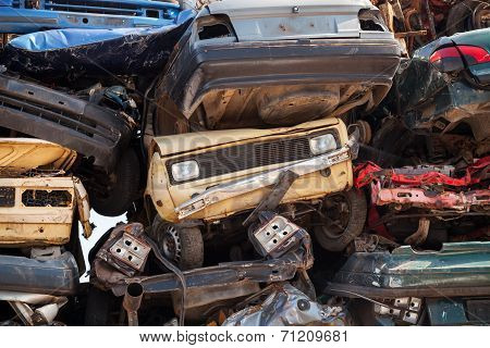 Abstract Background With Colorful Dump Of Stacked Cars In Junkyard