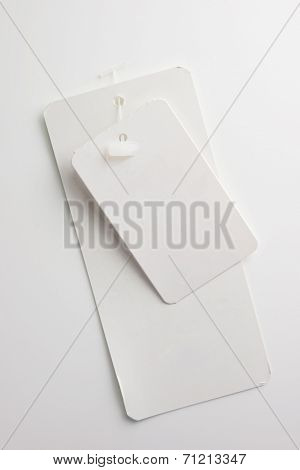 Two blank paper tags with attaching tag pin or tag fasteners. Description tag and a price tag, on natural white background. Focus is on the top tag.