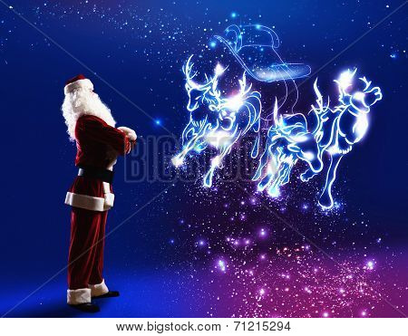 Santa claus looking at magic image of sledge with deer