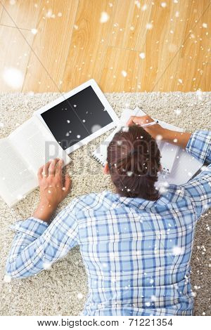 Brunette student doing assignments with her tablet against snow falling