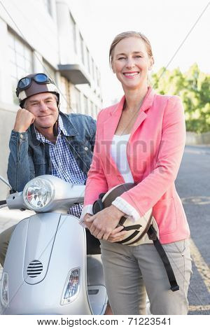 Happy senior couple posing with their moped on a sunny day